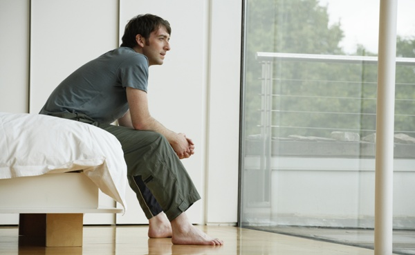 Young man sitting on edge of bed, looking out patio doors, side view