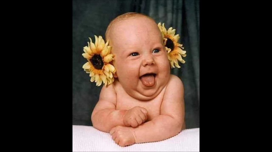 laughing baby with flowers in ears